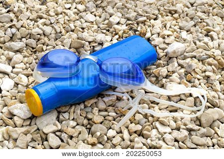 Swimming Goggles And Suntan Lotion On Pebble Beach.