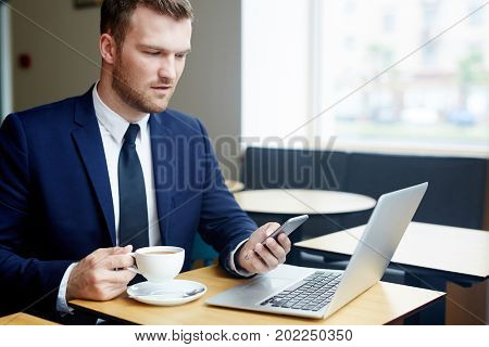 Young job-seeker with laptop and smartphone having tea in cafe