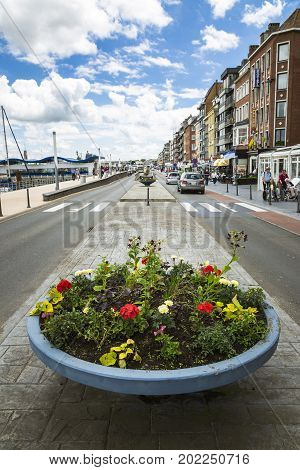 OOSTENDE BELGIUM - JUNE 22 2016: Wide vertical picture from a street near the pier with a vase with flowers in the foreground cars and people passing by in a sunny day with clouds. Oostende Belgium.