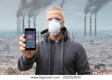 Man Showing Health Risk Rate On Cell Phone Against Smoke Emitting From Factory Chimneys