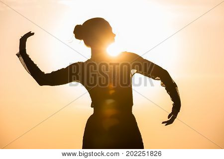 Silhouette of the woman dancing at the beach during beautiful sunrise