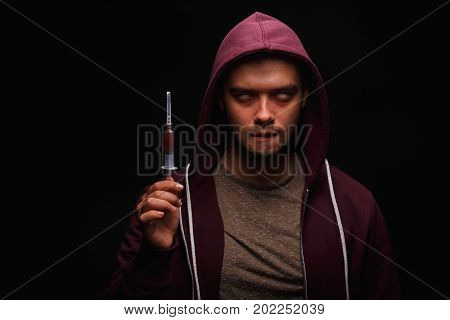 An unhappy man in a hood with a syringe full of narcotic substances on a saturated black background. A young man depends on drugs. An overdose of narcotics. Problems with illegal drugs. Copy space.