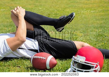 Close-up Of Injured American Football Player Lying On Field With Rugby And Helmet