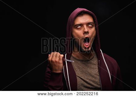 A drug addict male is holding syringe with narcotic drugs on a saturated black background. A drug user shooting up injecting of narcotics himself into the veins of his neck to satisfy his addiction.