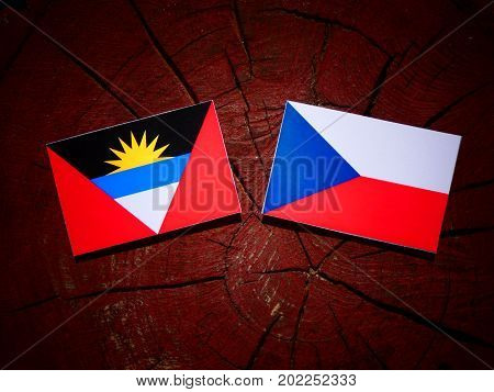 Antigua And Barbuda Flag With Czech Flag On A Tree Stump Isolated