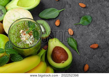 A view from above of a refreshing and exotic smoothie full of vitamins and kiwis on a gray table background. A composition from ripe bananas, organic avocado, cut kiwi and apple on a desk.