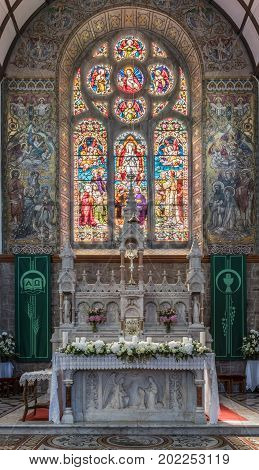 Galway Ireland - August 5 2017: Chancel with elaborate historic and new sober altar in front of painted and stained window backdrop in St. Mary's Church. White flowers candles and plenty of colors.