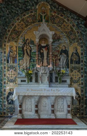Galway Ireland - August 5 2017: Side altar of St. Dominick in St. Mary's Church in front of painted backdrop and statue of said saint. Dark alcove plenty of other painted adoring saints.