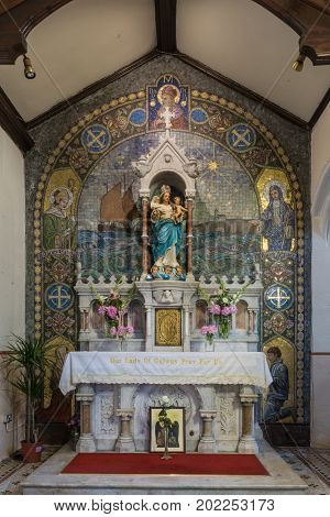 Galway Ireland - August 5 2017: Side altar of Mary and child in St. Mary's Church in front of painted backdrop and statue of said saint. Alcove plenty of other painted people ocean ship and city skyline.