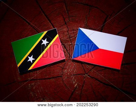 Saint Kitts And Nevis Flag With Czech Flag On A Tree Stump Isolated