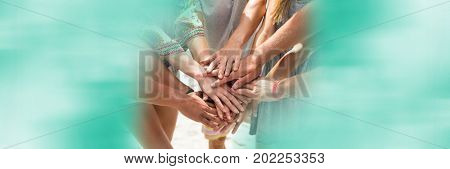 Digital composite of Hands together on beach and blurry teal framing