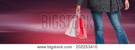 Digital composite of Shopper lower body with bags against blurry dark red background