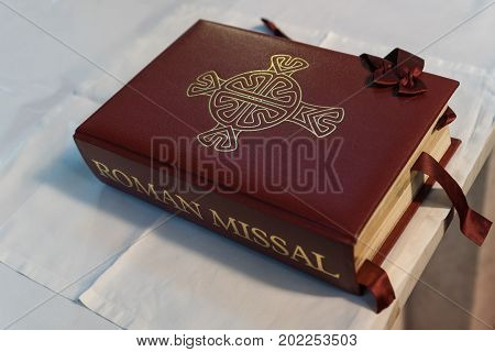 Galway Ireland - August 5 2017: Closeup of thick maroon Roman Missal on altar covered with white cloth.