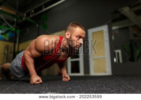 A photo of an attractive bodybuilder with a perfect muscular body does push-ups on a colorful gym background. A sexual young man pumping up his biceps on a floor. Fitness and healthy concept.