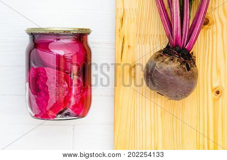 Glass jar with canned beets home made and fresh organic beets with haulm with cutting board on a white wooden background top view