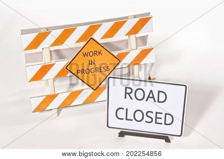 Construction warning barriers with Work in Progress and Road Closed signs over white background