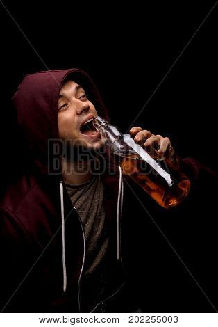 A satisfied male in a dark red hood is holding a huge bottle full of whiskey or liquor on a saturated black background. A boozed young man with a full bottle of alcoholic beverage.