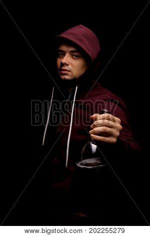 A satisfied male in a dark red hood is showing a huge bottle full of whiskey or liquor on a saturated black background. A boozed young man holding a full bottle of alcoholic beverage.