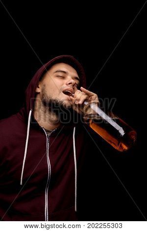 A laughing man wearing a dark red hoodie with a big transparent bottle full of alcoholic liquor on a saturated black background. A lonely male with whiskey, beer or scotch in his hands.