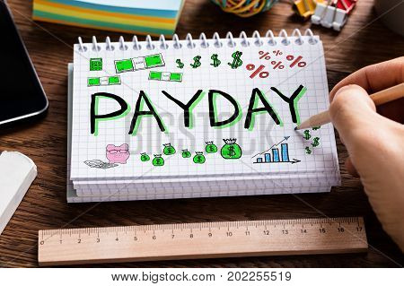 Man Drawing Payday Word In Notebook At Desk