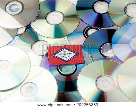 Arkansas Flag On Top Of Cd And Dvd Pile Isolated On White
