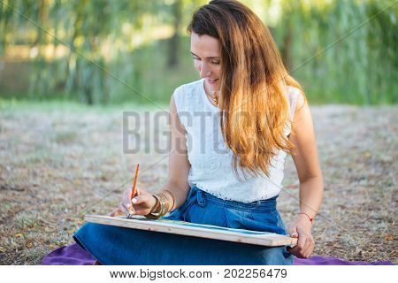 Charming woman sitting on plaid at the park in sunny sommer day and finishing draw picture by watercolor paints a beautiful landscape