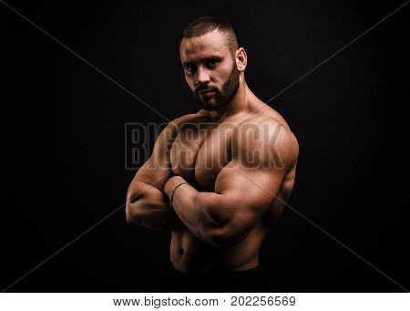 An attractive, sexy, stunning athlete with perfect muscles and posture. A bodybuilder showing off biceps and triceps on a black background. Gym, workout, exercising, building muscles concept.