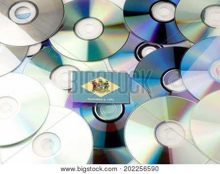 Delaware Flag On Top Of Cd And Dvd Pile Isolated On White