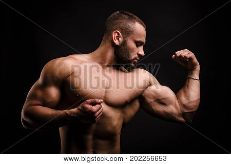 A fantastic macho man with muscular torso showing off his hand with perfect biceps and triceps after heavy exercises. A naked bodybuilder with strong abs working out hard on a black background. poster
