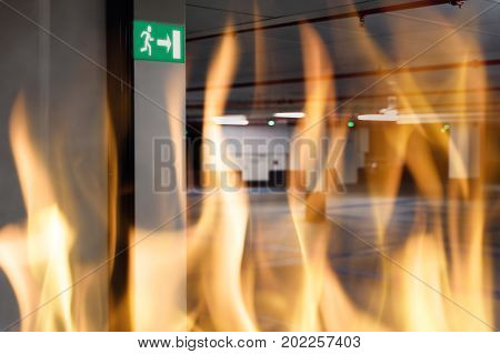 Fire against emergency exit sign at entrance of underground parking lot