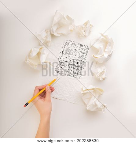 Female hand next to a few crumpled paper balls drawing charts and graphs