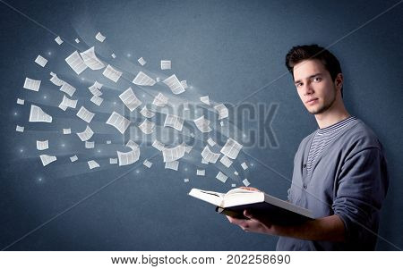 Casual young man holding book with pages flying out of it