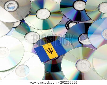 Barbados Flag On Top Of Cd And Dvd Pile Isolated On White