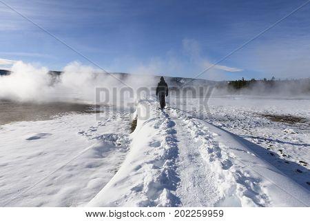 Man Walking Along Path in Winter at Old Faithful Geyser