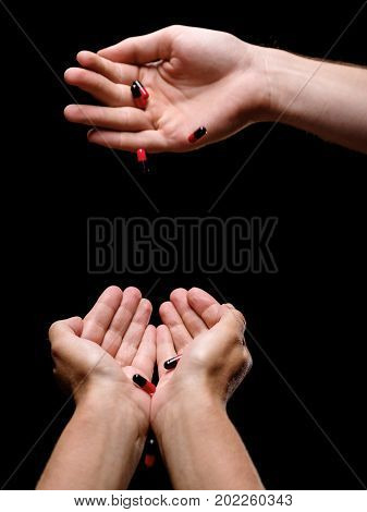 Composition of beautiful patient's palms receiving healthful medicaments from doctor's hand. Black and red capsules of antibiotics or drugs in palms on the black background. Professional medical help.