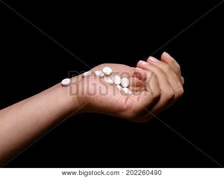 Close-up hand holding medical supplements on the black background. Different medications: pills, drugs, antibiotics, painkillers, narcotics, vitamins in tablets. White round prescripted aspirin.