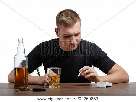 A stressed man is looking at a big glass full of brandy and a cigarette in his hands, isolated on a white background. A boozed guy with an alcoholic drink and pack of cigarettes on a wooden table.