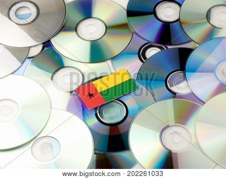 Guinea Bissau Flag On Top Of Cd And Dvd Pile Isolated On White