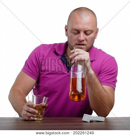 An addicted man in a crimson T-shirt is holding a big bottle and a transparent glass full of cognac, isolated on a white background. A lonely boozed guy with an alcoholic drink on a wooden table.