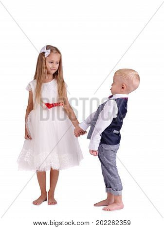 A full-length photo of a pretty couple of little children wearing classic clothes, isolated on a white background. A smiling girl in a white fluffy dress with red bow and a little boy in a gray suit.