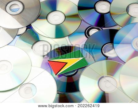 Guyana Flag On Top Of Cd And Dvd Pile Isolated On White
