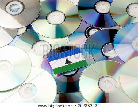 Lesotho Flag On Top Of Cd And Dvd Pile Isolated On White