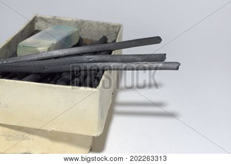 Natural Charcoal Sticks And Dirty Eraser In An Old Cardboard Box. Vintage Art Materials For Draw