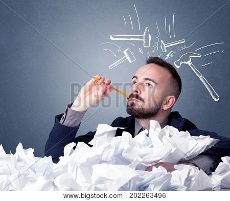 Young businessman sitting behind crumpled paper with drawn hammers hitting his head
