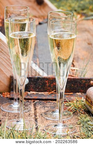 Four glasses of sparkling champagne sit on the landing near the docks of a river a lady's gold satchel sits nearby