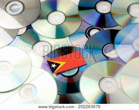 East Timorese Flag On Top Of Cd And Dvd Pile Isolated On White