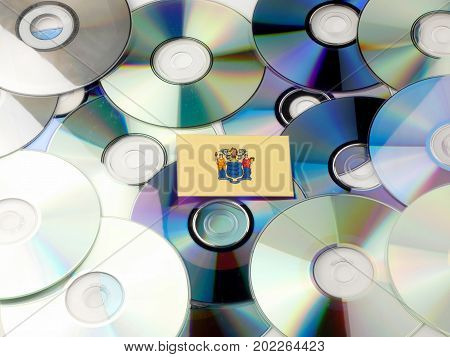 New Jersey Flag On Top Of Cd And Dvd Pile Isolated On White