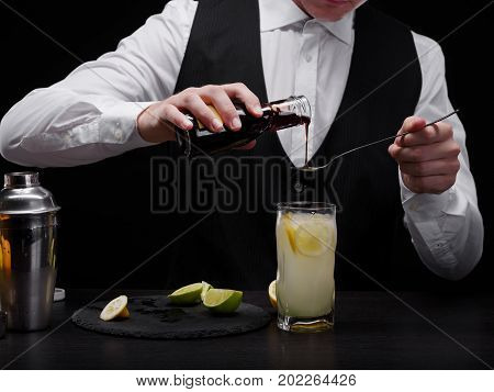 Elegant, classy bartender with a professional equipment for shakes on the black background. Close-up of a barman pouring thick juice in a tall a glass of alcoholic fruity beverage with limes and ice.