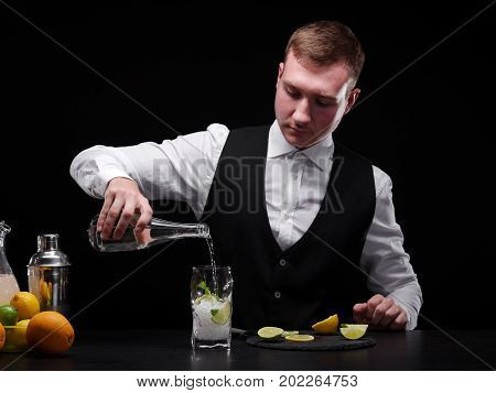 A handsome young bartender pouring Schweppes in a glass with ice and fruits on the black background. Barman behind a bar counter with sliced citrus fruits and empty glasses. Copy space.