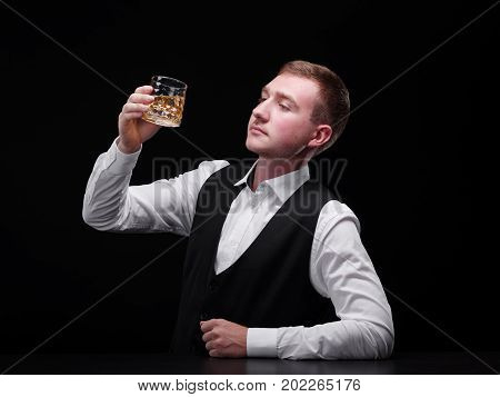 A young handsome bartender holding a fancy glass full of expensive liquor, whiskey or rum. A confident restaurant barkeeper behind bar counter drinking alcohol on the black background. Copy space.